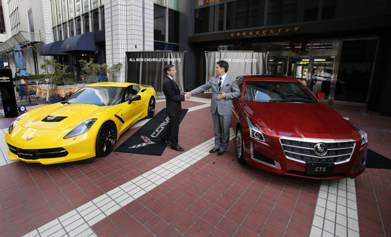 Sumito Ishii, managing director of General Motors Japan, center right, and Gregg Sedewitz, director of sales and marketing, shake hands after unveiling the new cars Cadillac CTS, right, and Chevrolet Corvette, left, to the media, in Tokyo, Japan, Wednesday, Dec. 4, 2013. General Motors Co. is focusing on pushing just the Cadillac and Corvette in Japan, not its other sprawling nameplates, honing in on a gradually growing but still niche breed of affluent entrepreneurs who aren't afraid to stand out. (AP Photo/Shuji Kajiyama)