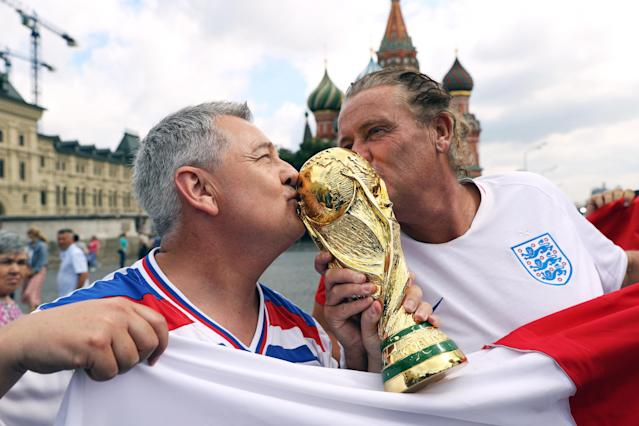 England fans pose for a picture with a replica World Cup trophy in Red Square ahead of the World Cup semi final. (PA)