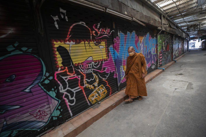 Thai Buddhist monk wearing a face mask to help curb the spread of the coronavirus walks pass closed shops in Khao San road, a popular hangout for Thais and tourists in Bangkok, Thailand Wednesday, Feb. 3, 2021. Amid fears of new variants of the virus, new restrictions on movement have hit just as people start to look ahead to what is usually a busy time of year for travel. (AP Photo/Sakchai Lalit)