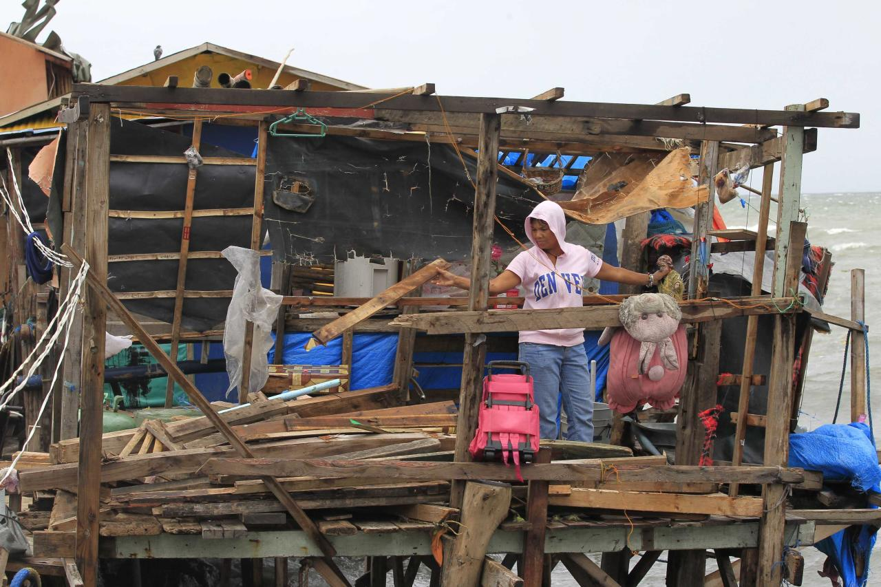 A resident salvages her belongings inside a damaged house after strong winds brought by Typhoon Rammasun (locally name Typhoon Glenda) battered the coastal area of Baseco compound, metro Manila July 17, 2014. The Philippines set to work clearing debris, reconnecting power and rebuilding flattened houses on Thursday after a typhoon swept across the country killing 38 people, with at least eight missing, rescue officials said. Typhoon Rammasun, the strongest storm to hit the Philippines this year, was heading towards China after cutting a path across the main island of Luzon, shutting down the capital and knocking down trees and power lines, causing widespread blackouts. REUTERS/Romeo Ranoco(PHILIPPINES - Tags: ENVIRONMENT DISASTER)