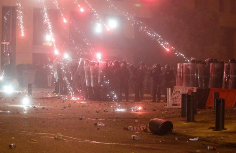 Fireworks are set off in front of police officers standing in position behind riot shields during a protest against a ruling elite accused of steering Lebanon towards economic crisis in Beirut