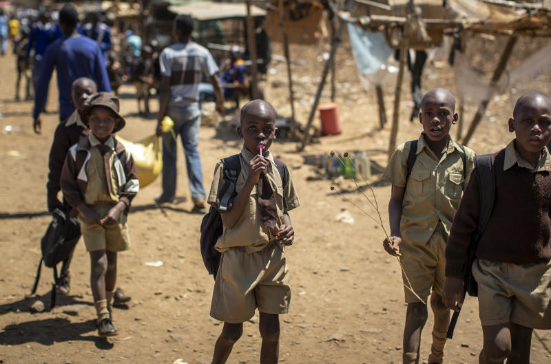 A schoolboy sucks on a lollipop as he and his friends walk back home on the first day of the school term, in Kuwadzana, on the outskirts of the capital Harare, in Zimbabwe Tuesday, Sept. 10, 2019. Former president Robert Mugabe, who enjoyed strong backing from Zimbabwe's people after taking over in 1980 but whose support waned following decades of repression, economic mismanagement and allegations of election-rigging, is expected to be buried on Sunday, state media reported. (AP Photo/Ben Curtis)