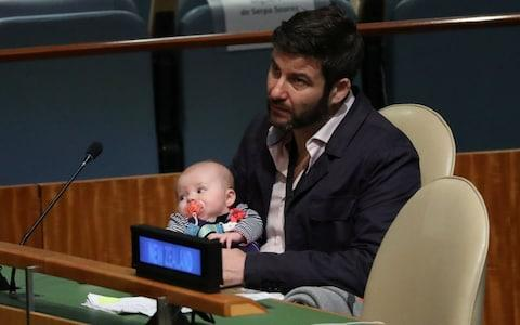 Clarke Gayford holds baby Neve while Jacinda Ardern speaks at the Nelson Mandela Peace Summit - Credit:  CARLO ALLEGRI/REUTERS
