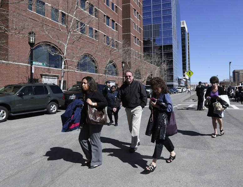 Employees flee from the Moakley Federal Court House as it is evacuated in Boston, Wednesday, April 17, 2013. The bombs that blew up seconds apart near the finish line of the Boston Marathon left the streets spattered with blood and glass, and gaping questions of who chose to attack at the Boston Marathon and why. (AP Photo/Charles Krupa)