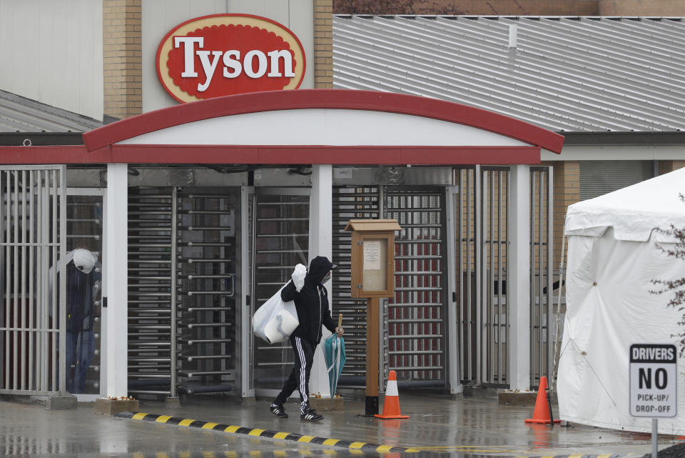 A Tyson Fresh Meats plant employee leaves the plant, Thursday, April 23, 2020, in Logansport, Ind. The plant will temporarily close its meatpacking plant in north-central Indiana after several employees tested positive for COVID-19. (AP Photo/Darron Cummings)