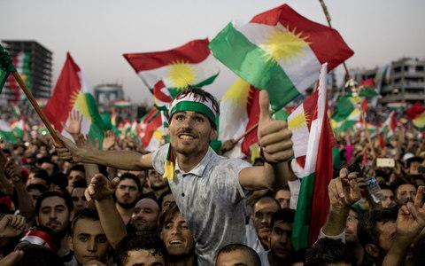 Supporters wave flags and chant slogans inside the Erbil Stadium while waiting to hear Kurdish President Masoud Barzani speak - Credit: Chris McGrath/Getty Images