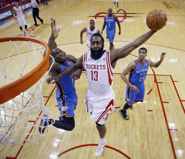 Houston Rockets' James Harden (13) goes up for a dunk as Oklahoma City Thunder's Serge Ibaka (9) defends during the first quarter of an NBA basketball game, Thursday, Jan. 16, 2014, in Houston. (AP Photo/David J. Phillip)