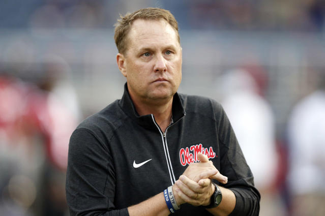 """FILE - In this Oct. 24, 2015, file photo, Mississippi football coach Hugh Freeze watches his team warmup before an NCAA college football game against Texas A&M in Oxford, Miss. Liberty has hired former Mississippi coach Hugh Freeze to lead its football program. A person familiar with the situation told The Associated Press that the Flames have tabbed Freeze as their next coach. The person spoke to the AP on the condition of anonymity because neither the school nor Freeze has publicly announced the decision. Liberty has scheduled a news conference to """"name Liberty's next head football coach"""" for Friday afternoon, Dec. 7, 2018. (AP Photo/Rogelio V. Solis, File)"""
