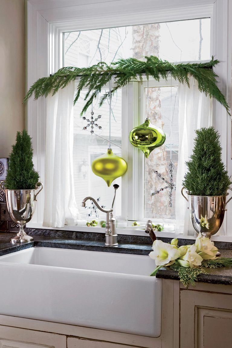 """<p>With some garland, a few ornaments, and a rosemary plant on either side, this window becomes the focal point of this cheery kitchen.</p><p><a class=""""link rapid-noclick-resp"""" href=""""https://www.amazon.com/s/ref=nb_sb_noss_2?url=search-alias%3Daps&field-keywords=christmas+ornaments&tag=syn-yahoo-20&ascsubtag=%5Bartid%7C10050.g.23343056%5Bsrc%7Cyahoo-us"""" rel=""""nofollow noopener"""" target=""""_blank"""" data-ylk=""""slk:SHOP CHRISTMAS ORNAMENTS"""">SHOP CHRISTMAS ORNAMENTS</a></p>"""
