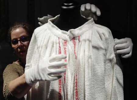 Curators Olivia Lichtscheidl (L) and Michael Wohlfart prepare a bathrobe owned by former Austrian empress Elisabeth for exhibition at Sisi museum in Vienna April 22, 2014. REUTERS/Heinz-Peter Bader