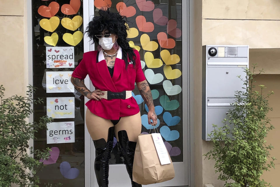 "This Friday, Aug. 28, 2020, photo shows Kochina Rude delivering food for customers in San Francisco. A San Francisco drag show night club has taken the show on the road after having to close its doors due to the coronavirus pandemic. Oasis' ""Meals on Heals"" is dispatching drag queens to deliver food, custom cocktails and socially-distant lip synch performances. (AP Photo/Haven Daley)"