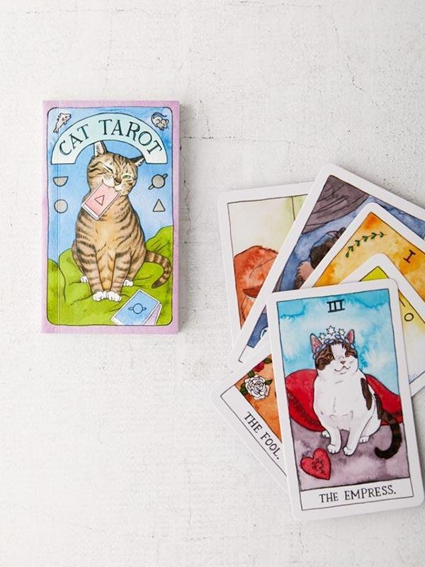 """Tarot cards + cats = the purr-fect present. $20, Urban Outfitters. <a href=""""https://www.urbanoutfitters.com/shop/cat-tarot-78-cards-and-guidebook-by-megan-lynn-kott?color=000&type=REGULAR&size=ONE%20SIZE&quantity=1"""" rel=""""nofollow noopener"""" target=""""_blank"""" data-ylk=""""slk:Get it now!"""" class=""""link rapid-noclick-resp"""">Get it now!</a>"""