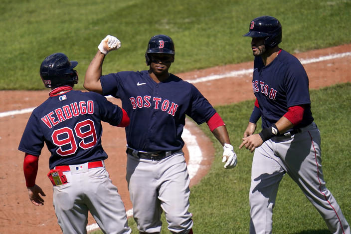 Boston Red Sox's Rafael Devers, center, celebrates his three-run home run with Alex Verdugo, left, and J.D. Martinez after he drove them home on a pitch by Baltimore Orioles pitcher Mac Sceroler during the fifth inning of a baseball game, Sunday, April 11, 2021, in Baltimore. (AP Photo/Julio Cortez)