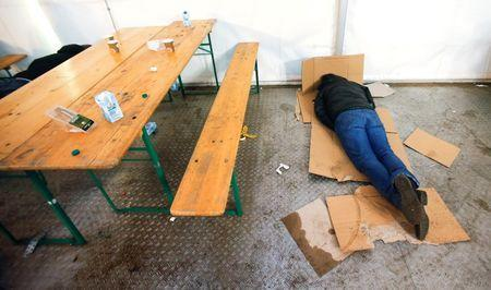 A migrant rests on cardboards at the the Berlin Office of Health and Social Affairs (LAGESO), in Berlin, Germany, January 5, 2016. REUTERS/Hannibal Hanschke