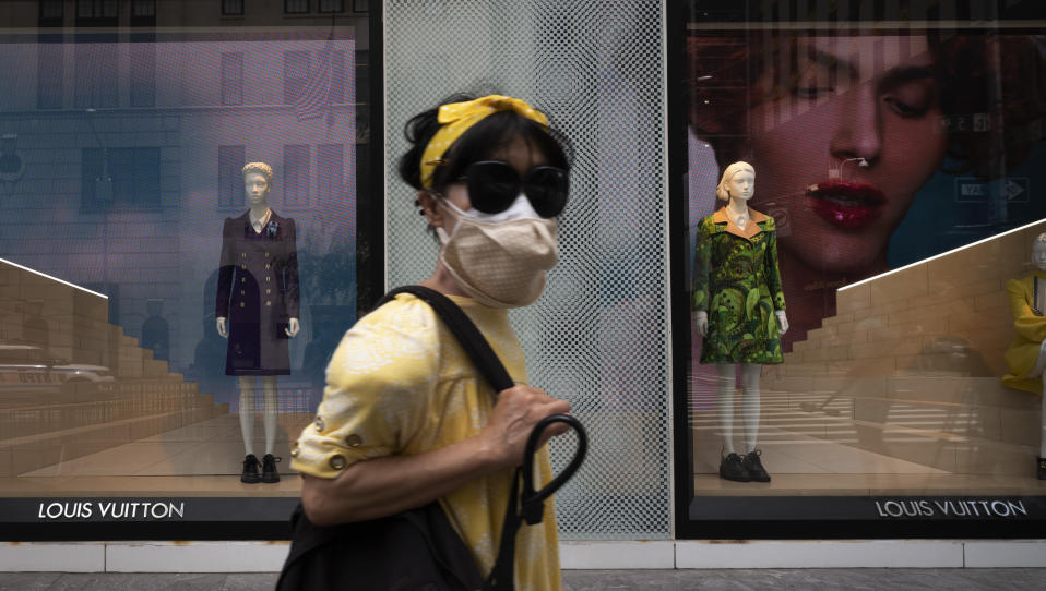 A woman wearing a mask walks by a Louis Vuitton store, Thursday, June 11, 2020, in New York's Fifth Avenue shopping district. The luxury goods store is open for curbside pickup. The New York City immortalized in song and scene has been swapped out for the last few months with the virus version. In all the unknowing of what the future holds, there's faith in that other quintessential facet of New York City: that the city will adapt. (AP Photo/Mark Lennihan)