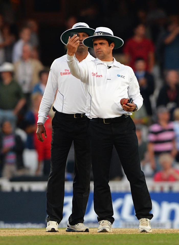 LONDON, ENGLAND - AUGUST 25: Umpires Aleem Dar (R) and Kumar Dharmasena take a light reading during day five of the 5th Investec Ashes Test match between England and Australia at the Kia Oval on August 25, 2013 in London, England. (Photo by Shaun Botterill/Getty Images)