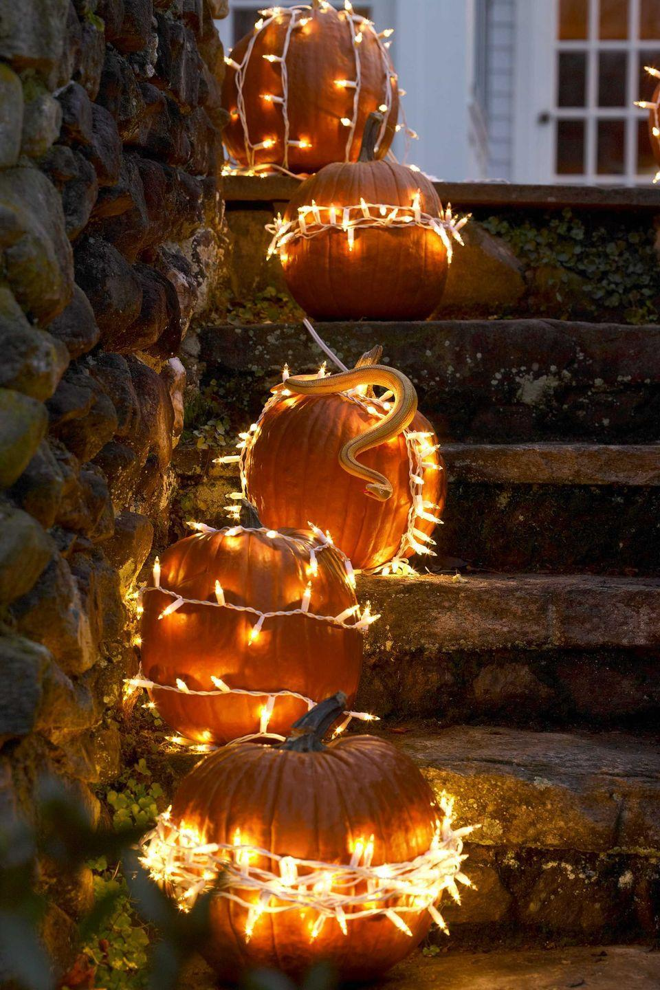 <p>Set your stoop ablaze by stringing white outdoor holiday lights around regular pumpkins. It's a simple way to set a spooky mood — and illuminate your walkway!</p>