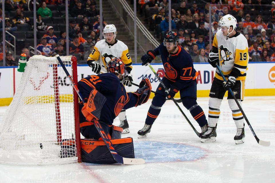 Edmonton Oilers goaltender Mike Smith (41) lets in a goal from Pittsburgh Penguins' Kris Letang, not seen, as Penguins' Teddy Blueger (53) and Jared McCann (19) watch during the third period of an NHL hockey game Friday, Dec. 20, 2019, in Edmonton, Alberta. (Codie McLachlan/The Canadian Press via AP)