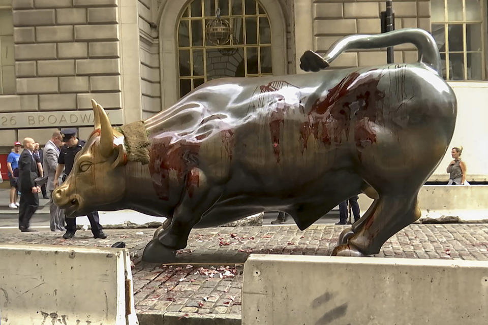 """In this freeze frame made from a video stage blood covers the iconic """"Charging Bull"""" statue near Wall Street on Monday Oct. 7, 2019, in New York. Demonstrators say they were protesting against a lack of government action against climate change. (AP Photo/Ted Shaffrey)"""