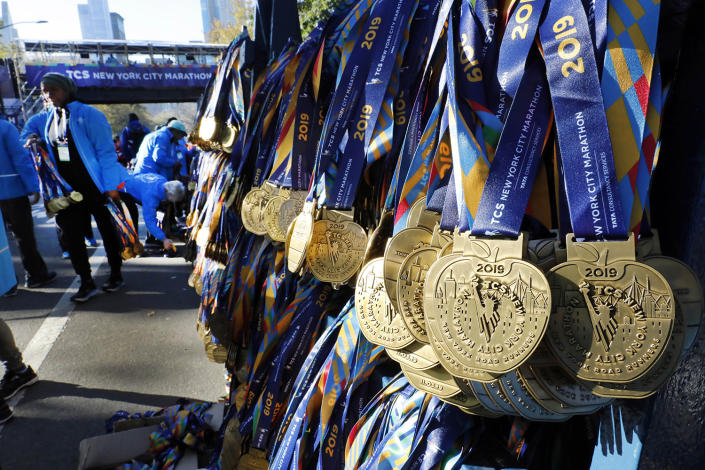 Volunteers hang medals for the finishers of the New York City Marathon, in New York's Central Park, Nov. 3, 2019. (Photo: Richard Drew/AP