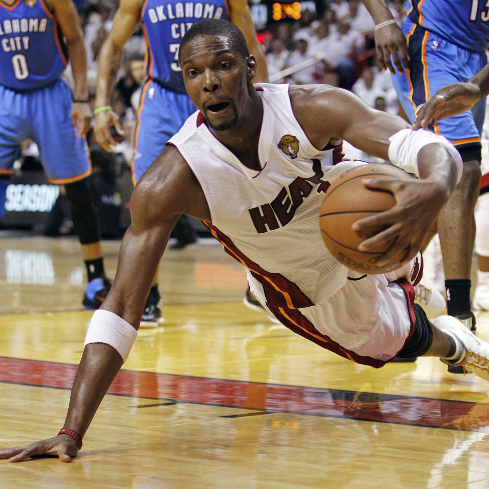 Miami Heat power forward Chris Bosh (1) dives for a loose ball against the Oklahoma City Thunder during the first half of Game 4 of the NBA Finals basketball series, Tuesday, June 19, 2012, in Miami. (AP Photo/Lynne Sladky)
