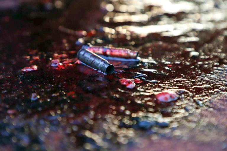 Ammunition shells lay on a pool of blood in a street of Culiacan (AFP Photo/RASHIDE FRIAS)