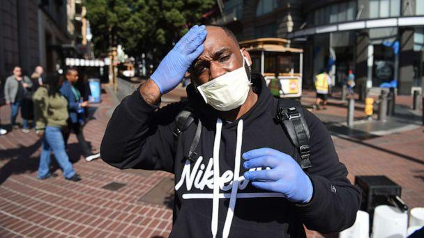 PHOTO: Cameron Nightingale adjusts his mask and gloves, a precaution to protect himself from coronavirus, in San Francisco on Feb. 27, 2020. (Josh Edelson/AFP via Getty Images)