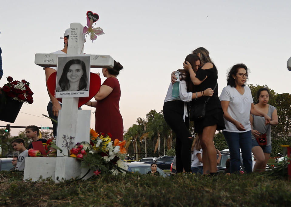 FILE - In this Feb. 18, 2018, file photo, Magaly Newcomb, right, comforts her daughter Haley Newcomb, 14, a student at Marjory Stoneman Douglas High School, at a memorial outside the school in Parkland, Fla. It's been more than 1,000 days since a gunman with an AR-15 rifle burst into the school, killing 17 people and wounding 17 others. And yet, with Valentine's Day on Sunday, Feb. 14, 2021, marking the three-year milestone, Nikolas Cruz's death penalty trial is in limbo. (AP Photo/Gerald Herbert, File)