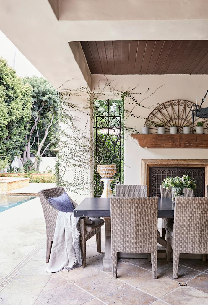 "<div class=""caption""> An outdoor dining room with a table and chairs from Restoration Hardware overlooks the pool. </div>"
