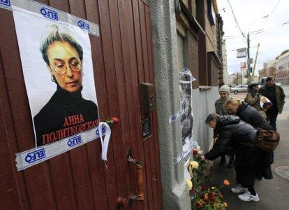 FILE PHOTO: People lay flowers next to a portrait of slain journalist Anna Politkovskaya on the sixth anniversary of her death, at her block of flats in central Moscow October 7, 2012. REUTERS/Sergei Karpukhin
