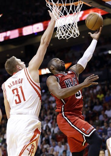 Miami Heat guard Dwyane Wade shoots against Houston Rockets center Cole Aldrich (31) during the first half of an NBA basketball game, Wednesday, Feb. 6, 2013, in Miami. (AP Photo/Wilfredo Lee)