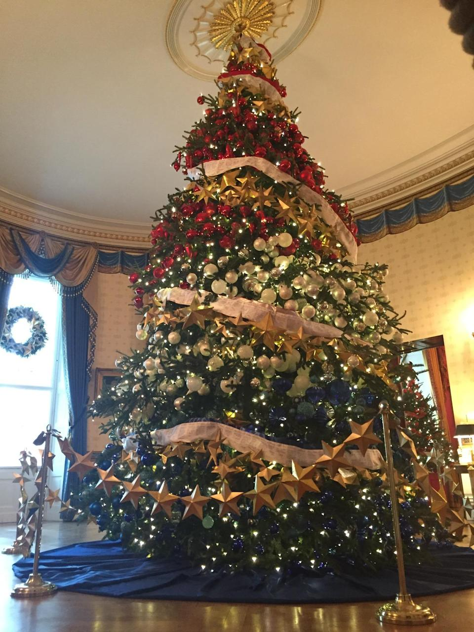 <p>Red, white, and blue ornaments cover the 18-foot-tall Frasier fir tree in the blue room of the White House. A ribbon covered in messages from military families is wrapped around the tree. <i>(Photo: Cassie Carothers)</i></p>