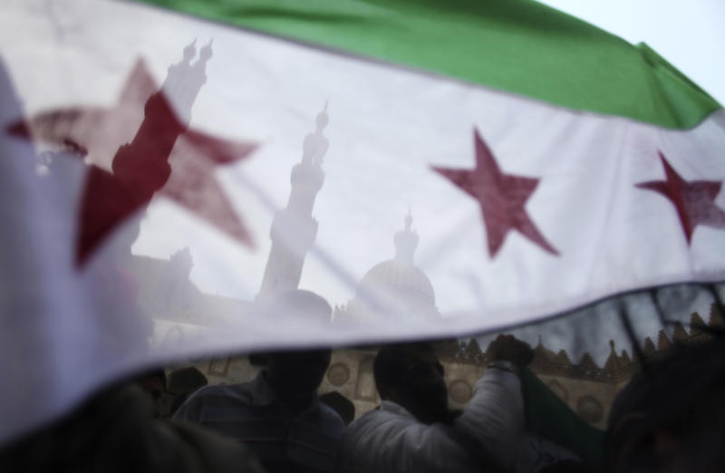FILE - In this Friday, Dec. 28, 2012 file photo, protesters wave the Syrian revolution flag during a rally after the Friday prayer at Al-Azhar mosque in Cairo, Egypt. Swept up in the Middle East's turbulent political winds, Syrians who fled their country's civil war are now increasingly gambling with their lives and life savings for a chance at a new start outside the region. A sharp rise in the number of Syrians attempting the perilous sea voyage over the past three months highlights the crushing life-and-death decisions facing many who fled to Egypt to escape Syria's armed conflict, according to rights group Amnesty International. (AP Photo/Khalil Hamra, File)