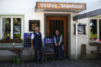 In this photo taken Thursday, May 7, 2020 brewery daughter Iris Detter and her father Karlmann stand in front of their 120 year old family brewery and traditional Bavarian restaurant in Altoetting, Germany. The 'Graminger Weissbraeu' brewery, which has been in the same family for a century, is preparing to welcome guests back to its restaurant for the first time in two months — with new rules and fears for the future. (AP Photo/Matthias Schrader)