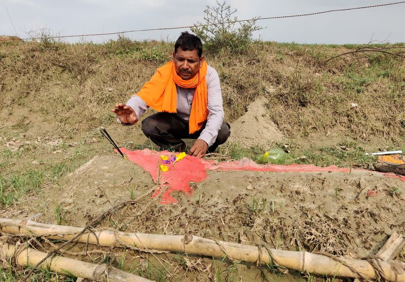 Govind Pasi, a grassroots worker for India's ruling BJP, prays next to the grave of his wife in Balai village