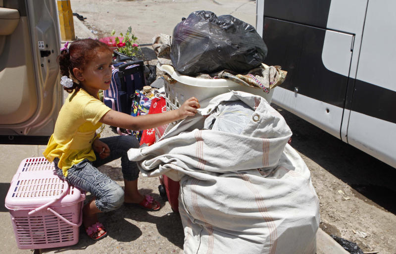 Layla Fadhil, an Iraqi refugee, sits with her family's belongings after her arrival from Syria to the Mansour neighborhood of Baghdad, Iraq, Friday, July 20, 2012. Iraq has flown hundreds of its citizens out of Damascus to escape the civil war in Syria, an official said Friday, while thousands of Iraqis poured through a major border crossing despite rebel takeovers of Syrian government posts and escalating violence near the two nations' boundaries. (AP Photo/Karim Kadim)