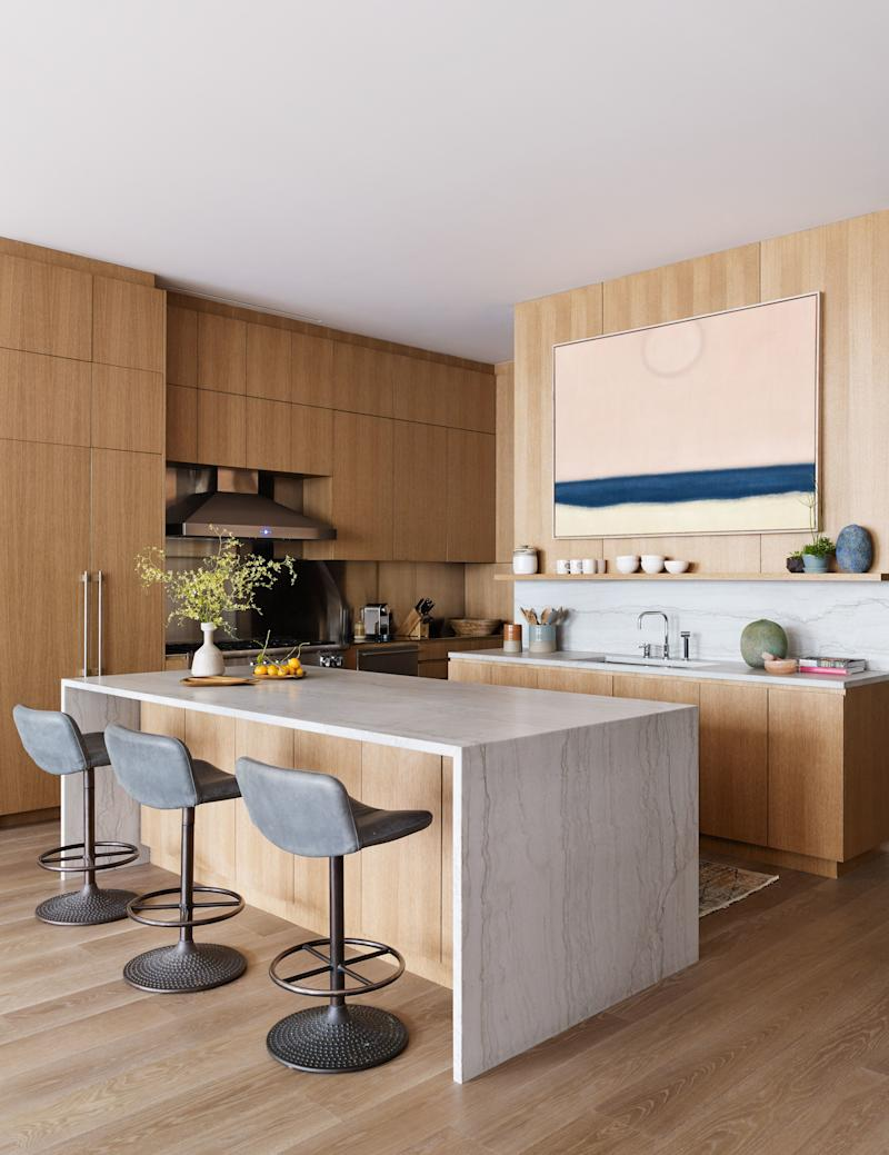 The custom kitchen cleverly marks the transition between the public and private spaces, and features an oversized quartzite island. The stools are by Ilmari Tapiovaara from Dual Modern. The painting is by Susan Vecsey.