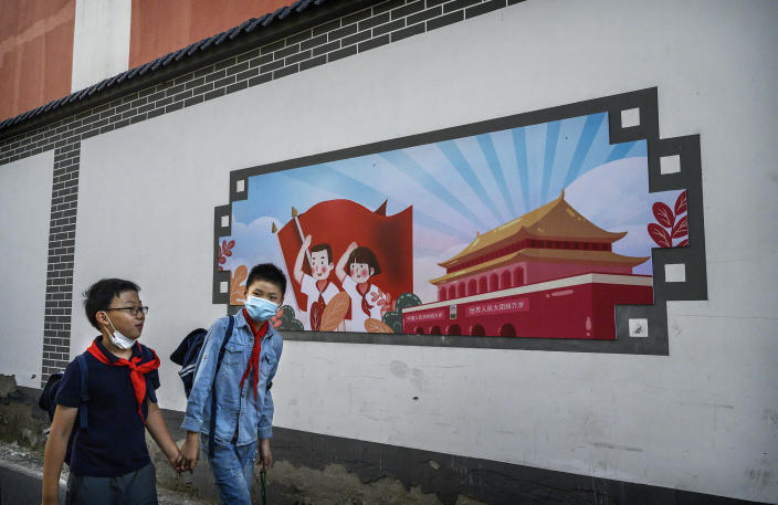 Image: Chinese boys pass a patriotic banner as they walk home together from a local elementary school after classes (Kevin Frayer / Getty Images file)