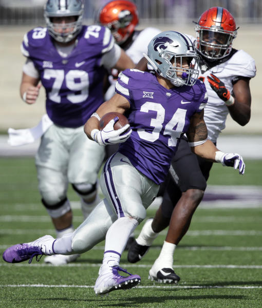 Kansas State running back Alex Barnes (34) gets past Oklahoma State linebacker Calvin Bundage, right, during the second half of an NCAA college football game in Manhattan, Kan., Saturday, Oct. 13, 2018. Kansas State won 31-12. (AP Photo/Orlin Wagner)