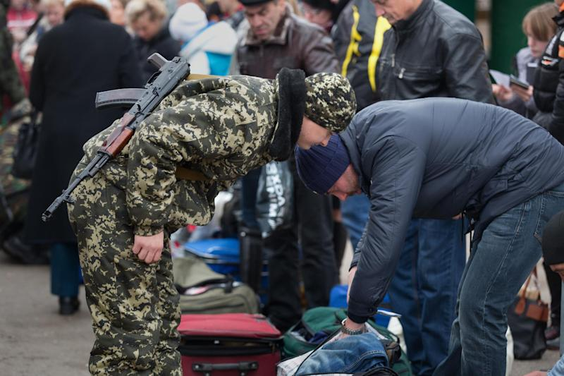 Border guards of the self-declared Donetsk People's Republic check passengers' luggage as they cross from East Ukraine into Russia at the border crossing of Uspenka, on November 15 2014 (AFP Photo/Menahem Kahana)