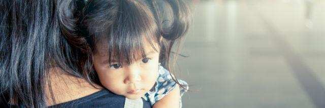 a little girl resting her chin on her mother's shoulder