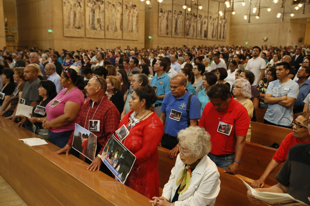 "Worshippers wear news photographs of immigrant children at the ""Mass in Recognition of All Immigrants"" at the Cathedral of Our Lady of the Angels in Los Angeles, Sunday, June 24, 2018. U.S. Customs and Border Patrol said it had reunited 522 children and that some were never taken into custody by Health and Human Services because their parents' criminal cases were processed too quickly. Officials have said as many as 2,300 children had been separated from the time the policy began until June 9. It's not clear if any of the 2,000 remaining children were taken into custody after June 9. (AP Photo/Damian Dovarganes)"