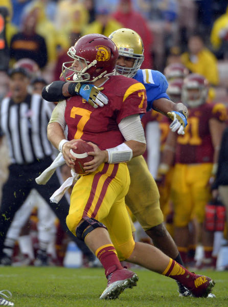 UCLA linebacker Anthony Barr, right, forces an incomplete pass as he grabs Southern California quarterback Matt Barkley during the second half of their NCAA college football game, Saturday, Nov. 17, 2012, in Pasadena, Calif. UCLA won 38-28. (AP Photo/Mark J. Terrill)