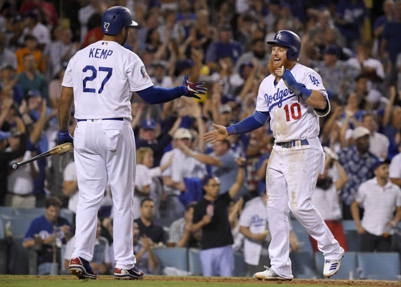 Los Angeles Dodgers' Justin Turner, right, celebrates with Matt Kemp after scoring on a double by Manny Machado during the seventh inning of a baseball game against the San Francisco Giants on Wednesday, Aug. 15, 2018, in Los Angeles. (AP Photo/Mark J. Terrill)
