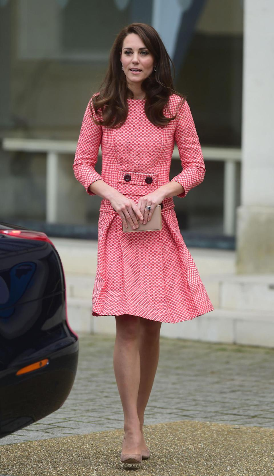 <p>For a charity visit to raise awareness of maternal mental health, Kate opted to re-wear a red skirt suit by Eponine London. The vintage style was first seen on the Duchess in March 2016 and features a box pleat skirt and 1960s detailing. She topped off the look with her favourite suede Gianvito Rossi heels and a nude box clutch by LK Bennett. </p><p><i>[Photo: PA]</i></p>