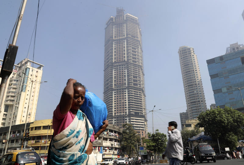 An Indian woman walks past an under construction building in Mumbai, India, Tuesday, Jan. 21, 2020. The IMF on Monday lowered India's economic growth estimate for the current fiscal to 4.8% and listed the country's Gross Domestic Product (GDP) numbers as the single biggest drag on its global growth forecast for two years. (AP Photo/Rafiq Maqbool)