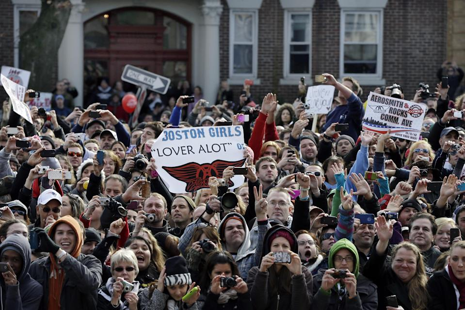 Fans line up along Commonwealth Avenue, Monday, Nov. 5, 2012 in Boston's Allston neighborhood to watch a free concert by Aerosmith whose band members lived there in the early 1970's. (AP Photo/Elise Amendola)
