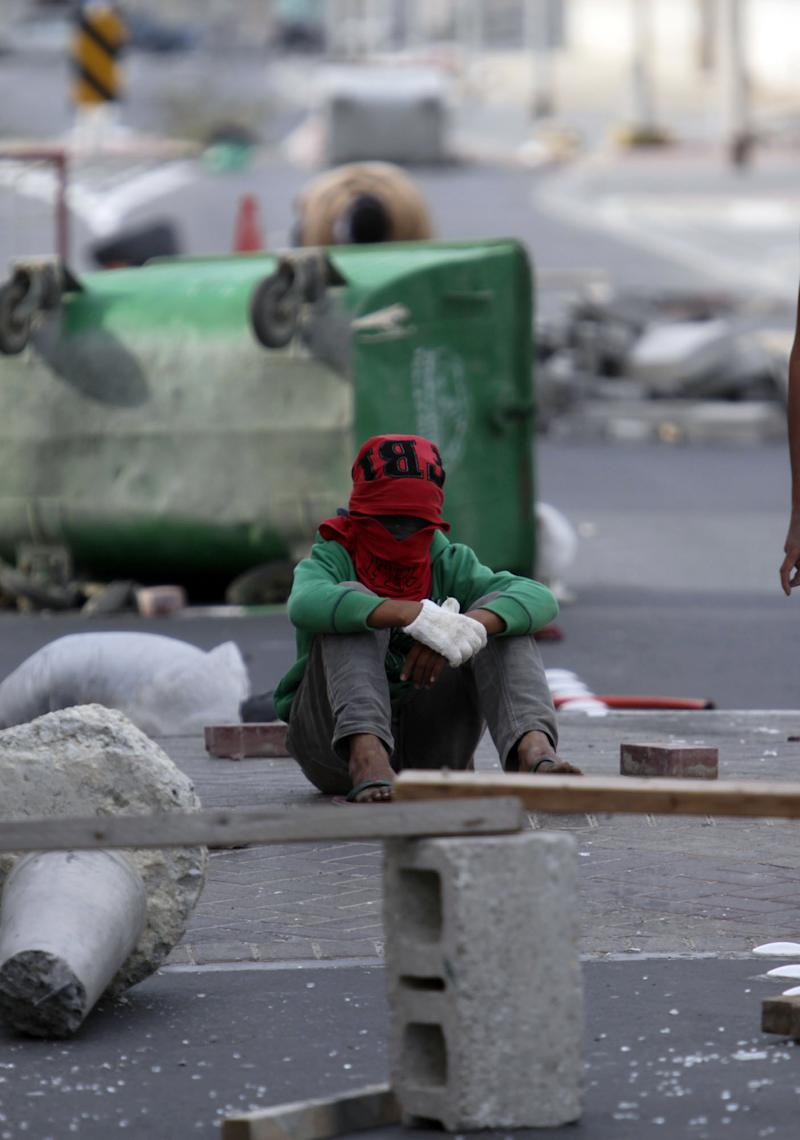 A Shiite Bahraini boy rests amid debris in the streets as people build barricades in the western village of Malkiya, Bahrain, on Wednesday, March 16, 2011,   in preparation for government-supporting forces who they expect will role into their Shiite Muslim village southwest of the capital of Manama. (AP Photo/Hasan Jamali)