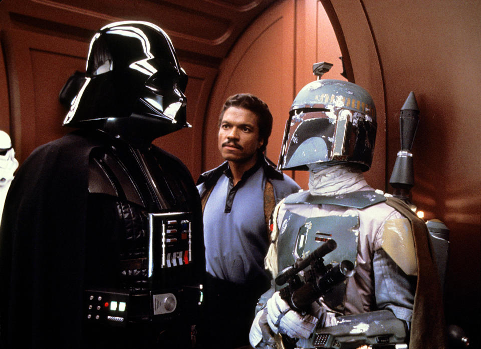 Darth Vader and Boba Fett strike a bargain while Lando Calrissian looks on in <em>The Empire Strikes Back</em>. (Photo: Lucasfilm/courtesy Everett Collection)