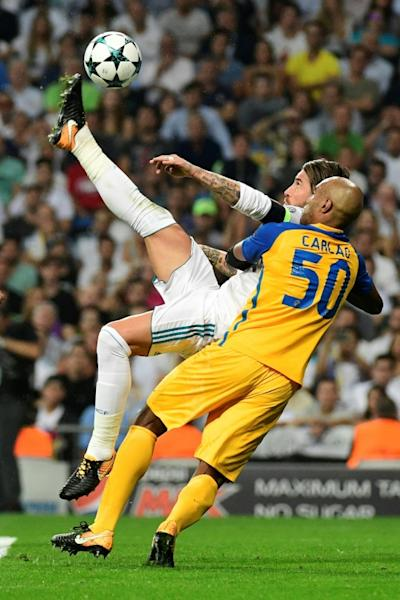 Real Madrid's defender Sergio Ramos (L) scores during a UEFA Champions League football match against APOEL at the Santiago Bernabeu stadium in Madrid on September 13, 2017